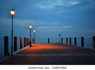 Wooden bridge on the night surrounded by lit street lamps. The bridge is on the lake Garda.