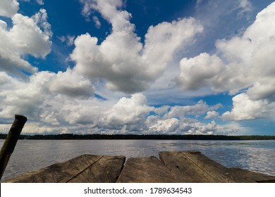 Wooden bridge on the river against the background of clouds