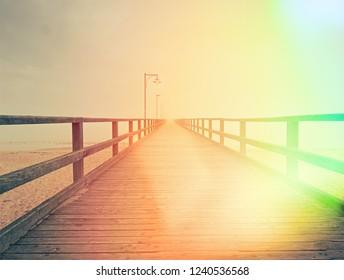Wooden bridge on a sea dock. Pier on the coastline. Sea coast.  Hipster filter.