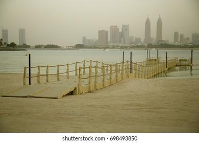Wooden bridge on the sea water. Dubai Marina