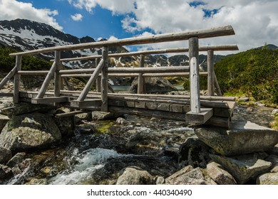 wooden bridge over alpine lake in Tatra mountains at summer time.