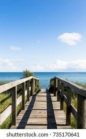 wooden bridge over dune to the shore