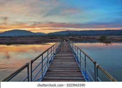 The wooden bridge over the river and moutain in background with sunlight reflected on lake at sunset. Beautiful landscape nature scene on twilight.