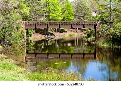 A wooden bridge over a river with reflections