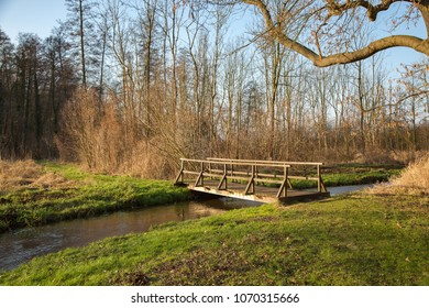 Wooden bridge over small river in Brody, Poland