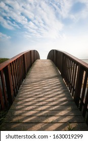 Wooden bridge over water and sand, on the North Sea coastline, in sunlight, on Sylt island, Germany. Wooden pathway towards the sky. Summer wandering