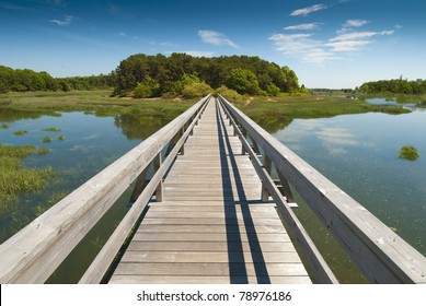Wooden bridge in perspective leading to an enchanted island on old Cape Cod