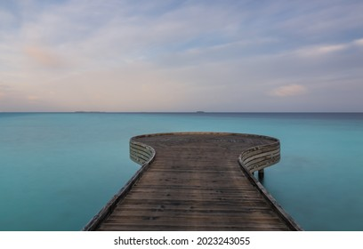 Wooden bridge or pier on tropical white sand beach with clear blue ocean and sky on sunny day. Boardwalk into the ocean and turquoise water. Summer holidays background with copy space. Crossroads