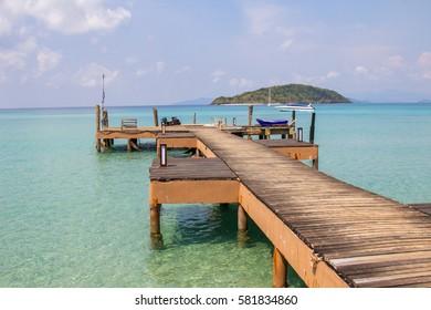 Wooden bridge pier stretch on clear aqua blue sea