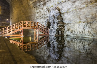 Wooden bridge reflexion in underground salt mine lake