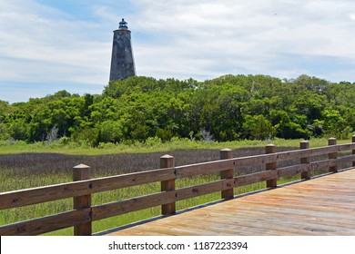 A wooden bridge runs in front of Old Baldy Lighthouse, Bald Head Island, North Carolina