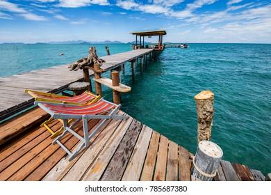 The wooden bridge in the sea has an indigo sky as the background.