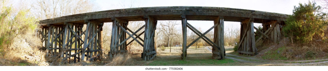 A wooden bridge spanning a small valley at Sunset. View with shadows of bridge in the open spaces.