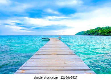 The wooden bridge stretches into the sea.With  Mountain clouds and sky.