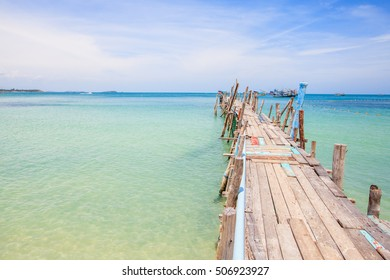 Wooden bridge that stretches down to the sea in boats.