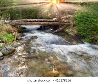 Wooden bridge in the Ukrainian Carpathians, on a stormy mountain river to go to the shepherds and flocks of sheep in the pasture - polonina. Traditional wooden logs of spruce strong