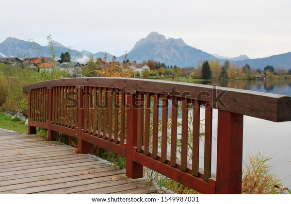 Wooden brigen along a lake in a landscape in fall, mountains in the background, Allgäu, Bavaria