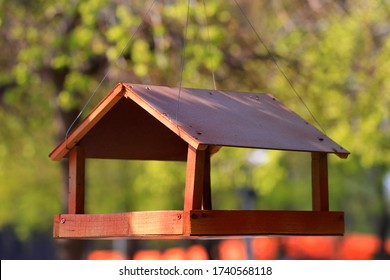 Wooden brown birdhouse, manger hanging on a tree in a spring park. Wild Bird Care, Home, and Food. Bird nest in spring