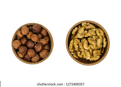 Wooden brown bowl with hazelnuts and wallnuts isolated on white background. The view from the top.