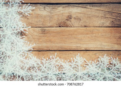 Wooden brown christmas background and white snowflakes with space.