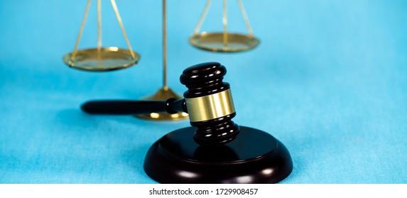 Wooden brown judges gavel on blue background