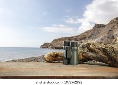 Wooden brown table and summer ladnscape. Green binoculars and free space for your decoration.