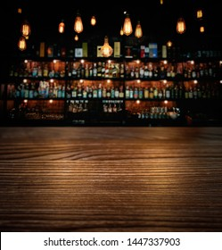 Wooden brown table and vintage lamps with blurred liquor bar background