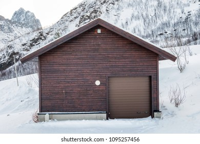 Wooden brown warehouse with roll door on snow hill