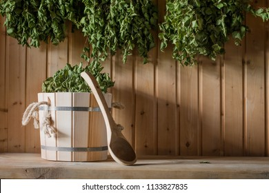A wooden bucket and a birch broom in a Russian bath. Sauna. Free space on a wooden background.