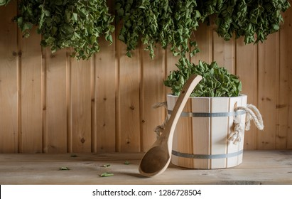 A wooden bucket and a birch broom in a Russian bath. Sauna. Free space on a wooden background mock up