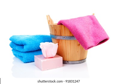 wooden bucket for spa or sauna with colorful towels and soap over white background