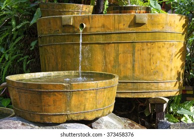 Wooden buckets with water flowing from one to another