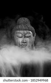 Wooden Buddha head in smoke on black, b/w.