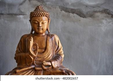 Wooden buddha statue, on grey cement background