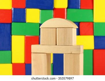wooden building bricks in front of block wall