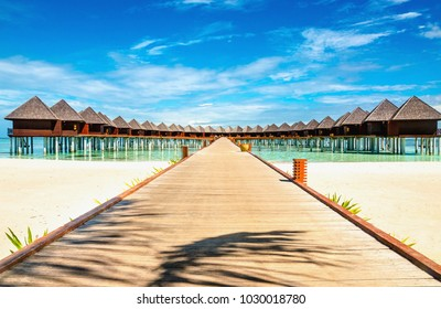 Wooden bungalow on the background of azure water and blue sky, Maldives