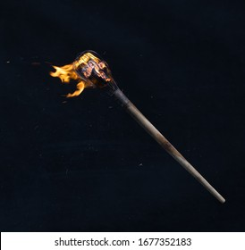 wooden burning torch on a black background