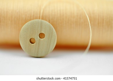 Wooden button and yellow thread