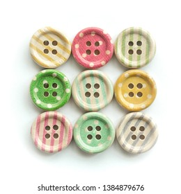 Wooden buttons with colorful stripes and colorful dots on a white background. Sewing