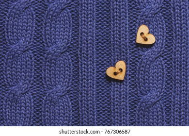 Wooden buttons on heart on knitted wool blue background. Valentine's Day.