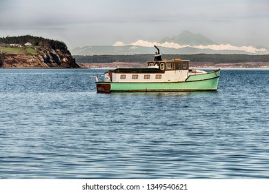 A wooden cabin cruiser at anchor in Puget Sound with the Cascade Mountains in the background.