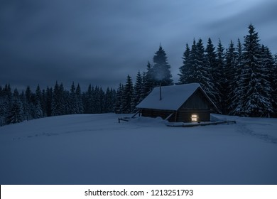 Wooden cabin under stars. Lights shines through the window from inside of the house. Night landscape in winter. Smoke goes from the chimney.