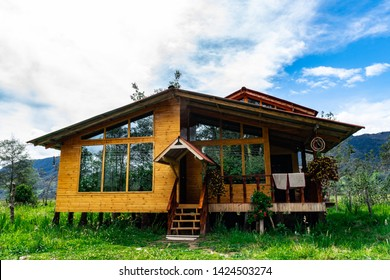 The wooden cabin with windows kind of mirrors some luxury. This house has atrapasueños in the exterior and a lot plants. It's a home of a farmer or a person lover at field.