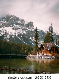 Wooden cabin in winter evergreen forest at Emerald Lake in Yoho National Park, Canada with a wooden bridge over the lake and snow-covered mountains in the background