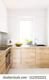 Wooden cabinets in bright minimal white kitchen interior with window. Real photo