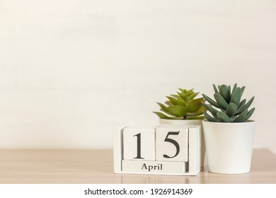 A wooden calendar with the date April 15 on the desktop.
