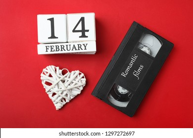 Wooden calendar with date of February 14, decorative white heart and old retro cassette on bright red background. Watching romantic movie. Concept Valentine's day. Top view.