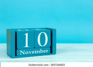wooden calendar with the date of November 10 on a blue wooden background, International Day of Embroiderers; World Youth Day; World Science Day; International day of accounting