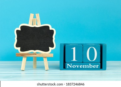 wooden calendar with the date of October 10 and an easel on a blue background, place for text, International Day of Embroiderers; World Youth Day; World Science Day; International day of accounting