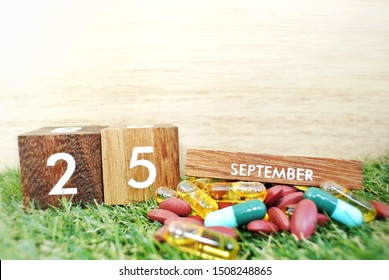 Wooden calendar on September 25 and medicine on the wooden background, the concept of World Pharmacist Day